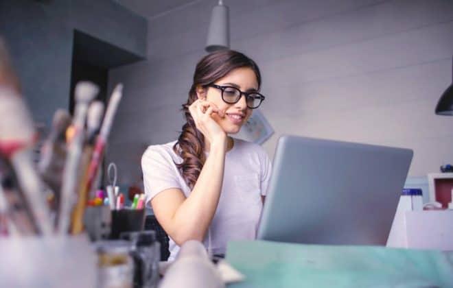 Frau sitzt in ihrem Arbeitszimmer an einem Laptop